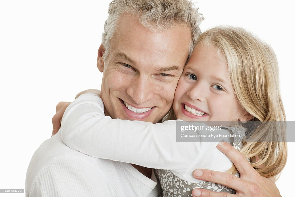 Portrait of father and daughter hugging, smiling : Stock Photo
