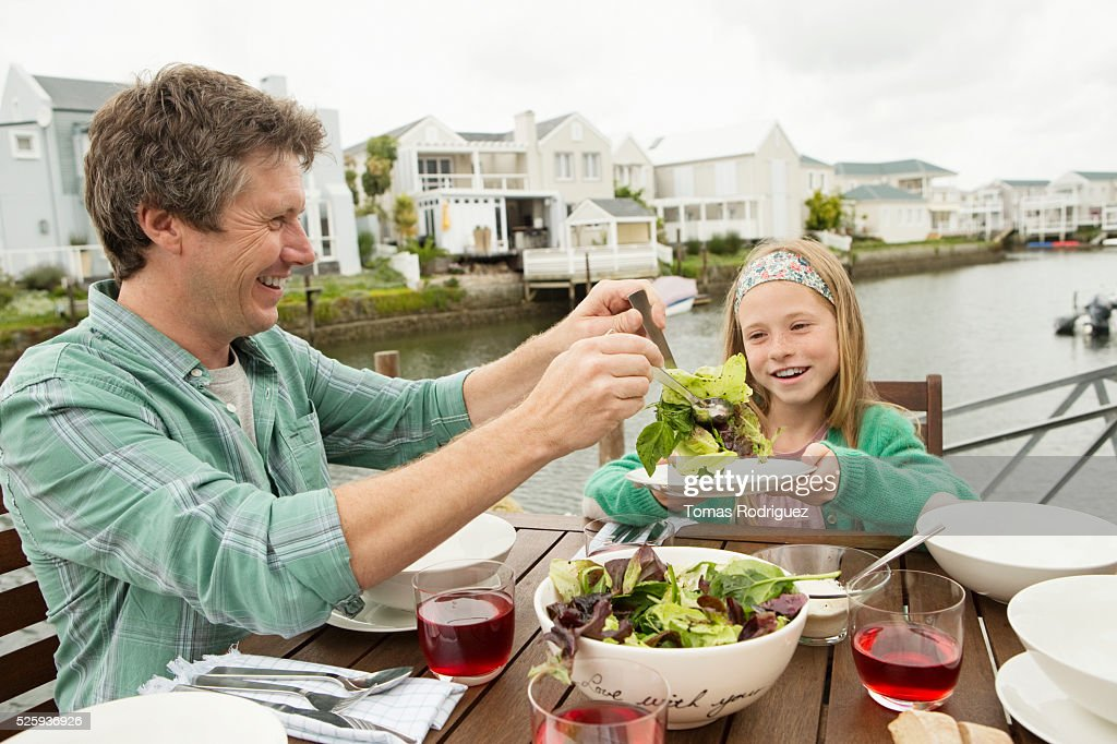 Portrait of father and girl (8-9) eating outdoors : Stock Photo