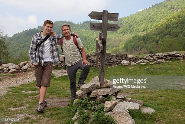 Portrait of father and son beside hiker's sign