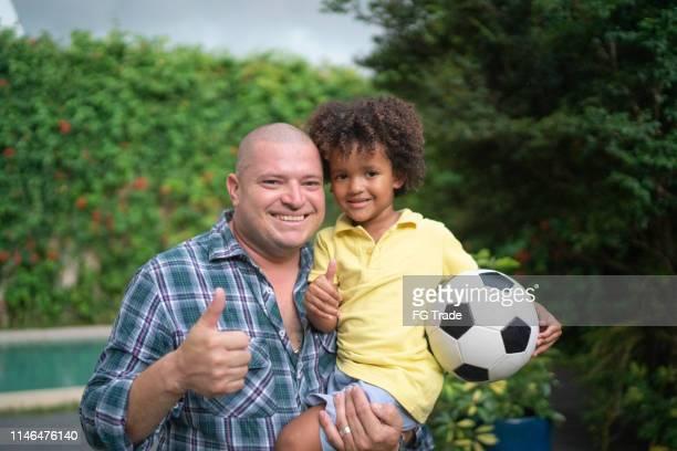 retrato do pai e do filho, menino que prende uma esfera de futebol - latino americano - fotografias e filmes do acervo