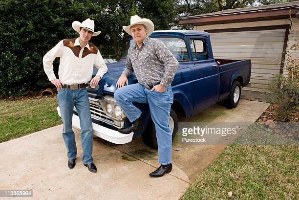 Portrait of father and son by a pick-up truck in front of house