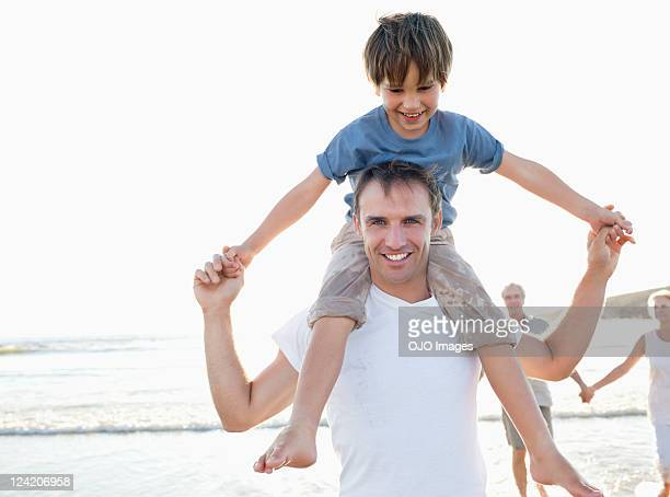 Portrait of father and son enjoying on beach with grandparents in background