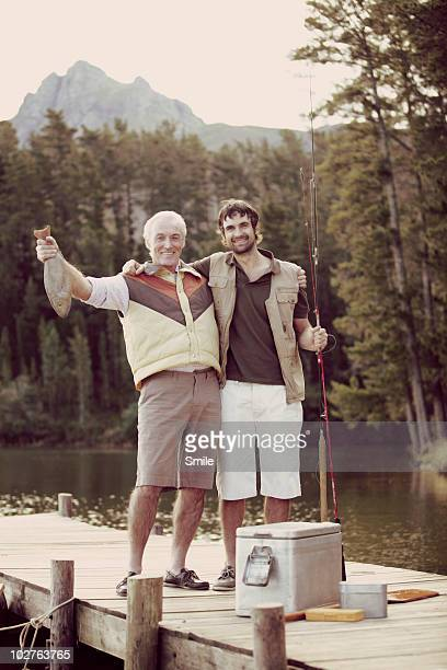 Portrait of father and son holding fish on jetty