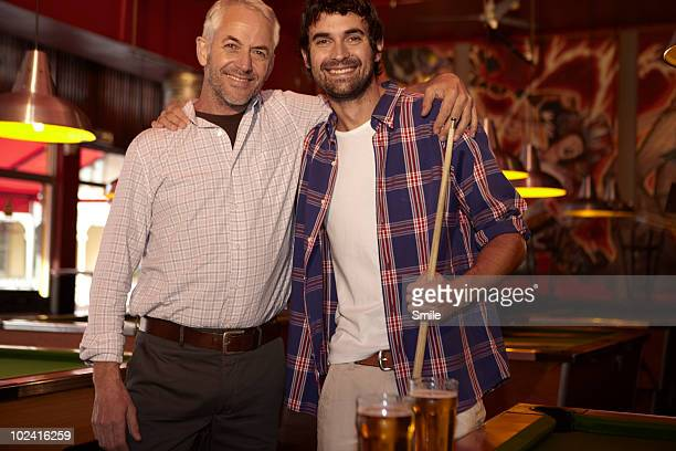 Portrait of father and son in pool bar