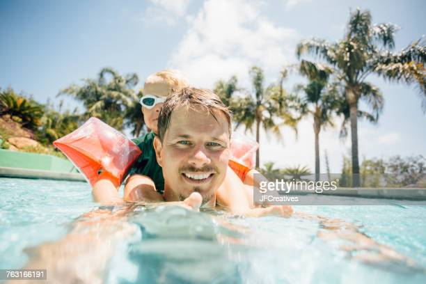 portrait of father and son in swimming pool - taking the plunge stock photos and pictures
