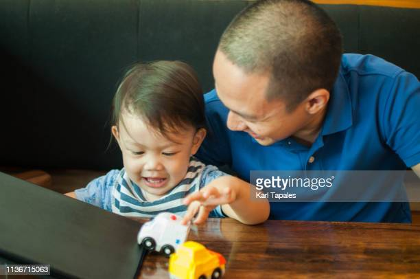 a portrait of father and son indoor - daily life in philippines stock pictures, royalty-free photos & images