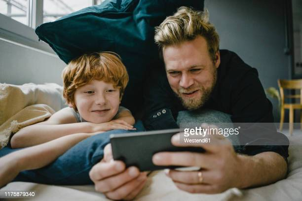 portrait of father and son lying on couch looking at cell phone - sohn stock-fotos und bilder