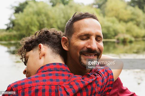 Portrait of father and son, outdoors, hugging