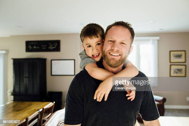 portrait of father and son piggybacking while standing at home - cavan images foto e immagini stock