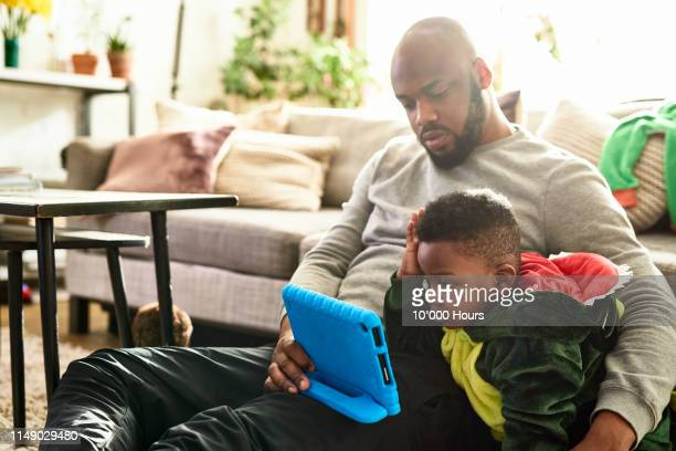 portrait of father and son relaxing with digital tablet - candid stock pictures, royalty-free photos & images
