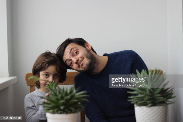 Portrait Of Father And Son Sitting With Houseplants At Home