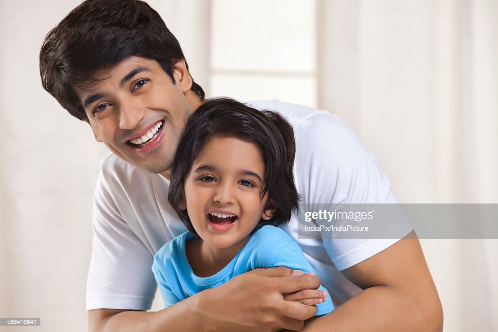 Portrait of father and son smiling : Stock Photo
