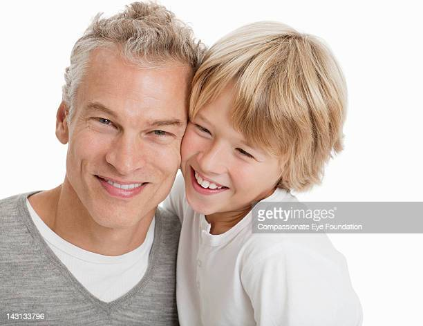 Portrait of father and son, smiling, studio shot