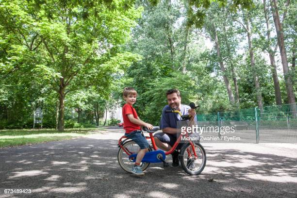 Portrait Of Father And Son With Bicycle At Park