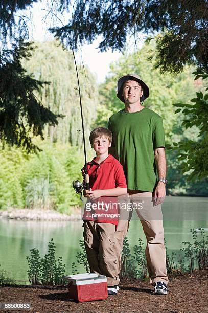 Portrait of father and son with fishing pole