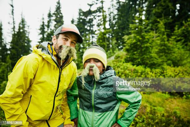 portrait of father and son with mustaches made of moss during camping trip - naughty america stock pictures, royalty-free photos & images