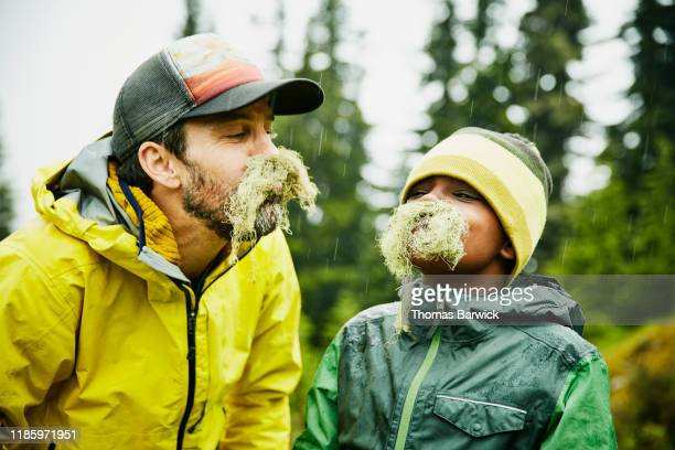 portrait of father and son with mustaches made of moss during camping trip - day 7 stockfoto's en -beelden