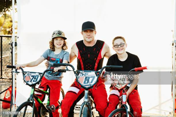 Portrait of father and sons sitting on BMX bikes before race
