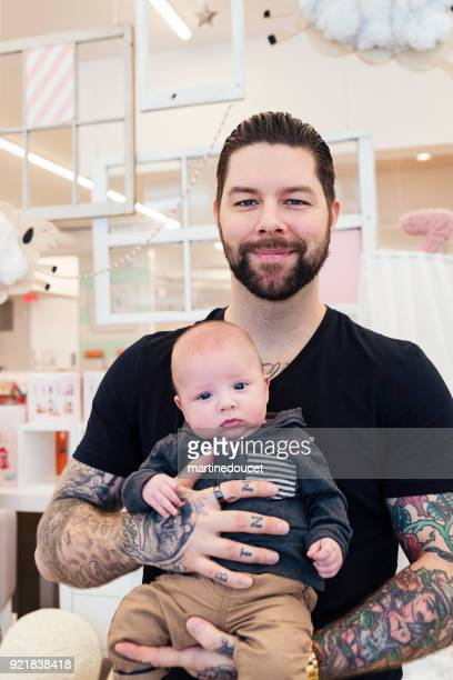 Portrait of father and young baby in a children store.