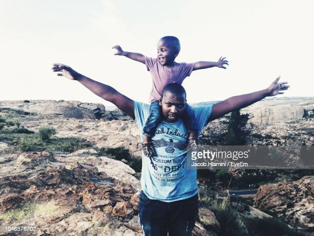 portrait of father carrying son on shoulder while standing against clear sky - carrying on shoulders stock pictures, royalty-free photos & images