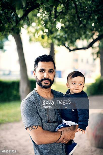 Portrait of father carrying toddler while standing at park