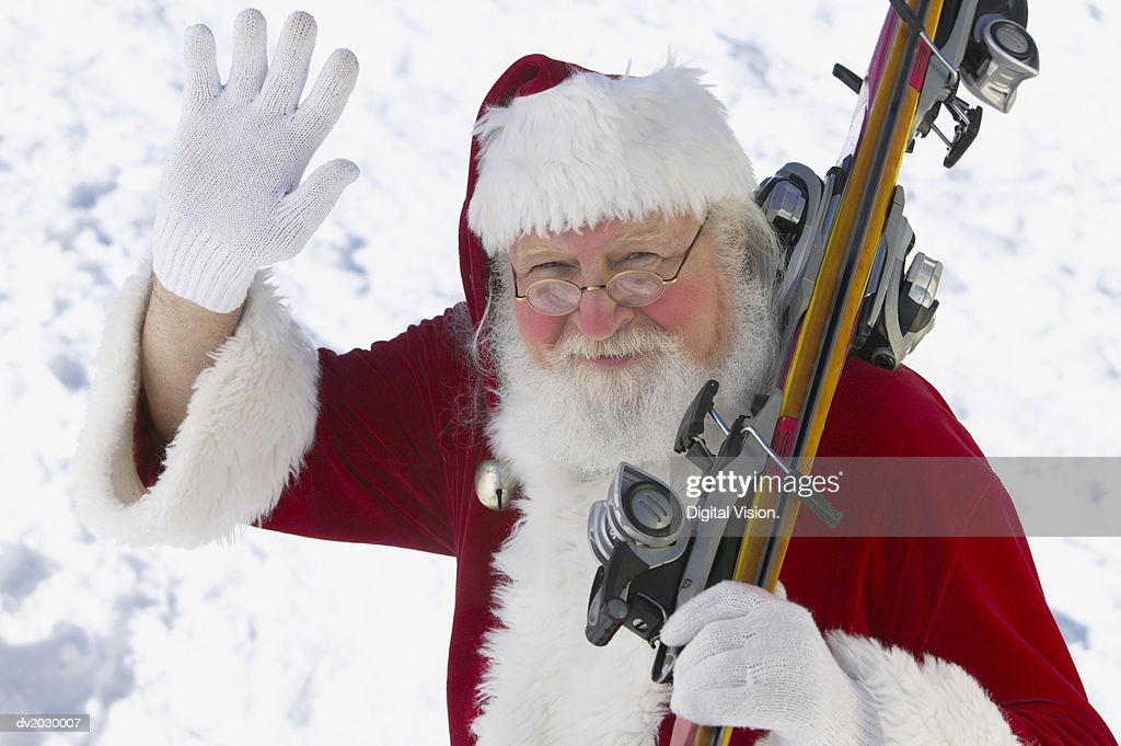 Portrait of Father Christmas Holding Skis and Waving : Stock Photo