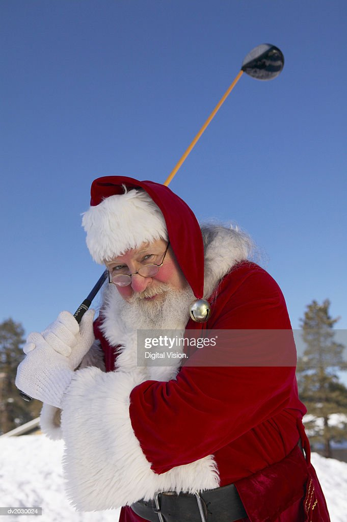 Portrait of Father Christmas Standing in the Snow With a Golf Club : Stock Photo