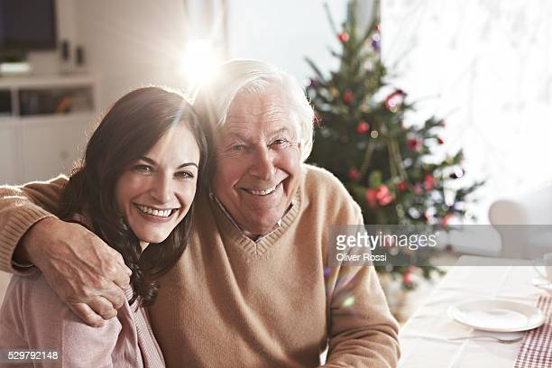 Portrait of father embracing adult daughter at Christmas table