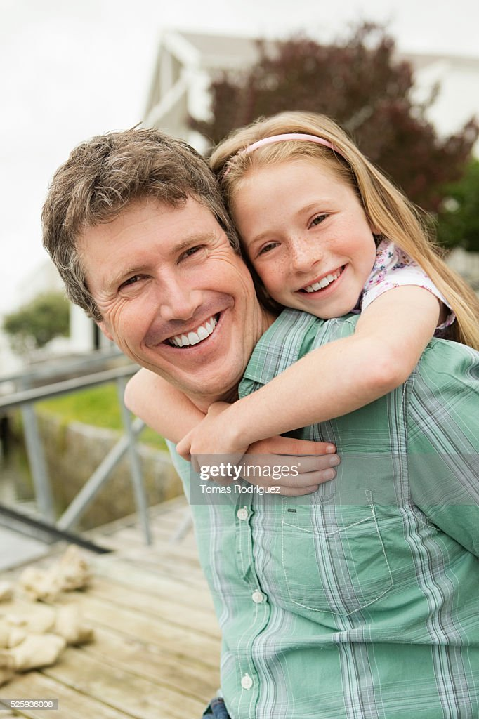Portrait of father giving daughter (8-9) piggyback ride : Stock Photo