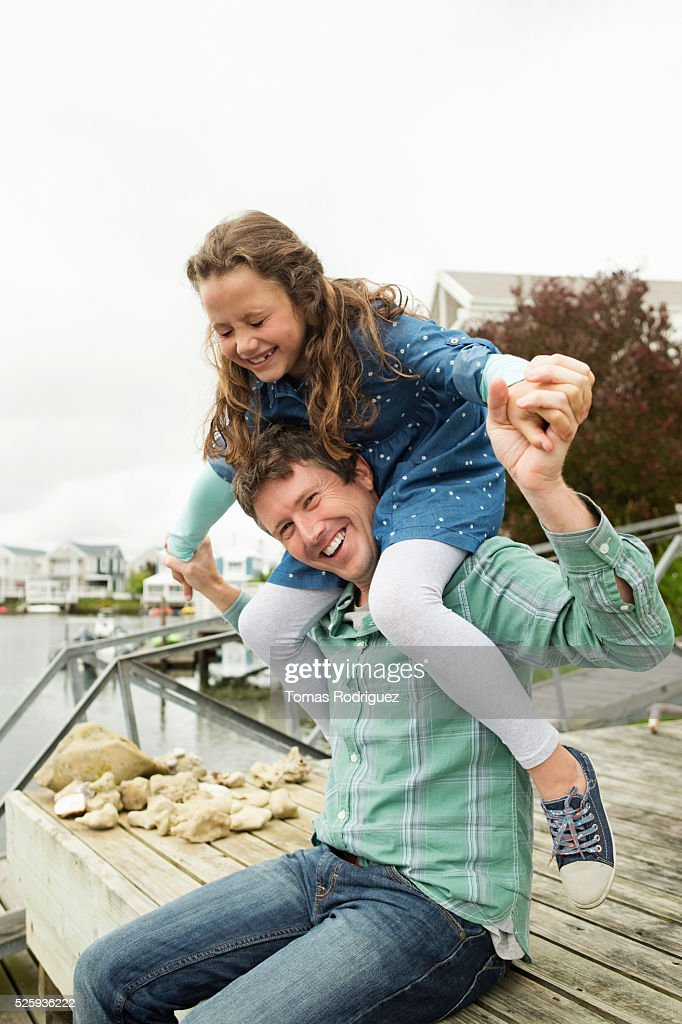 Portrait of father giving daughter (6-7) piggyback ride : Foto stock