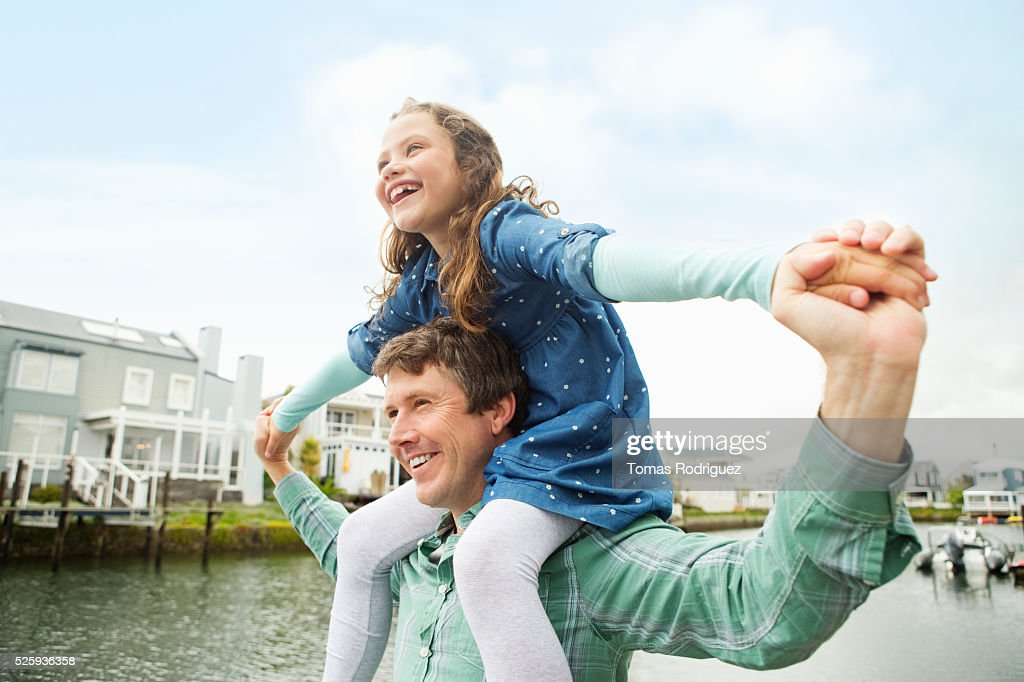 Portrait of father giving daughter (6-7) piggyback ride : Foto de stock
