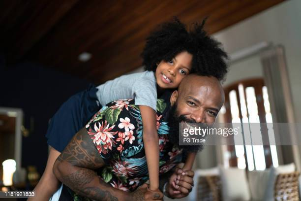 portrait of father giving his daughter a piggyback ride - fathers day stock pictures, royalty-free photos & images