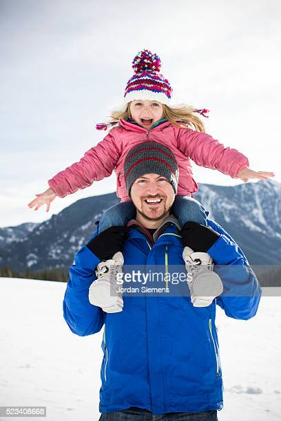 portrait of father giving piggy back ride to daughter (4-5), bozeman, gallatin county, montana, usa - bozeman stock pictures, royalty-free photos & images