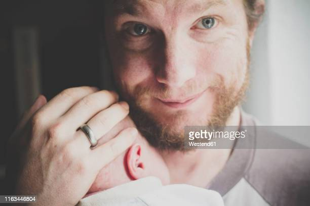 portrait of father holding his one-week-old son - zärtlich stock-fotos und bilder