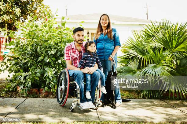 Portrait of father in wheelchair posing with family and dog in front of home