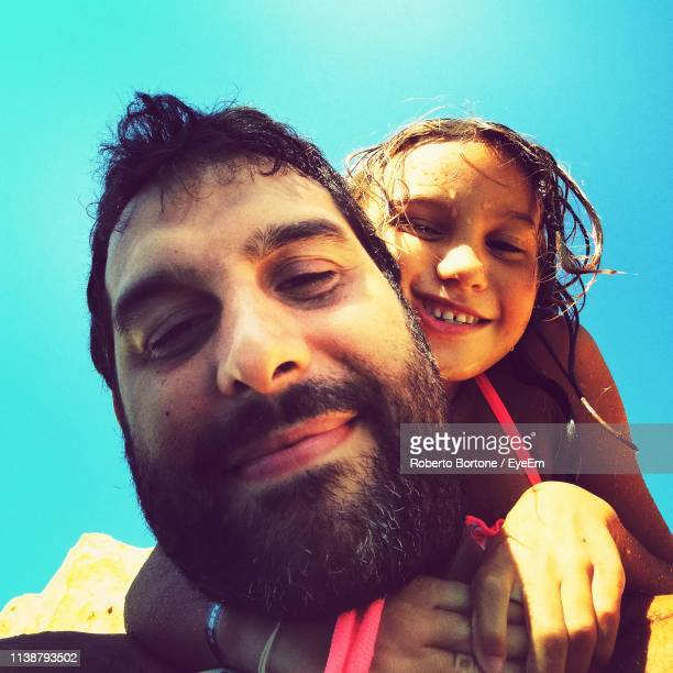 Portrait Of Father With Daughter Against Sky