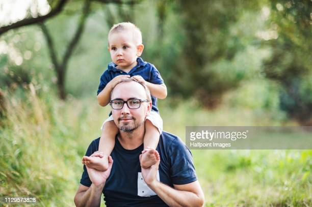 A portrait of father with glasses giving a toddler boy a piggyback ride outdoors in nature in summer.