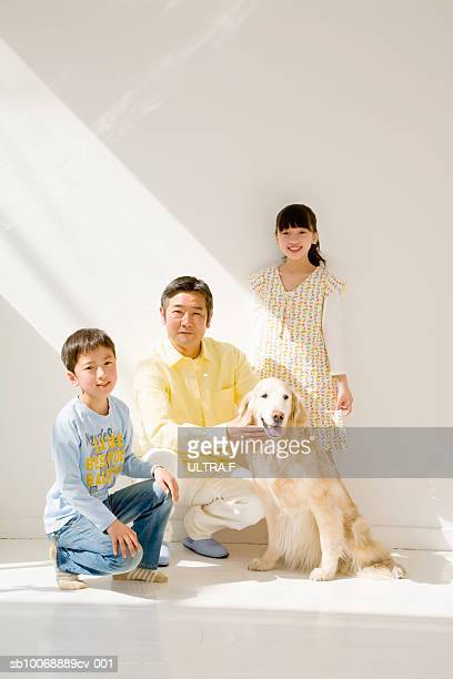 Portrait of father with son and daughter (8-10) in room with dog