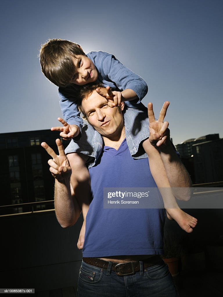 Portrait of father with son (8-9), boy sitting on man's shoulders : Foto stock