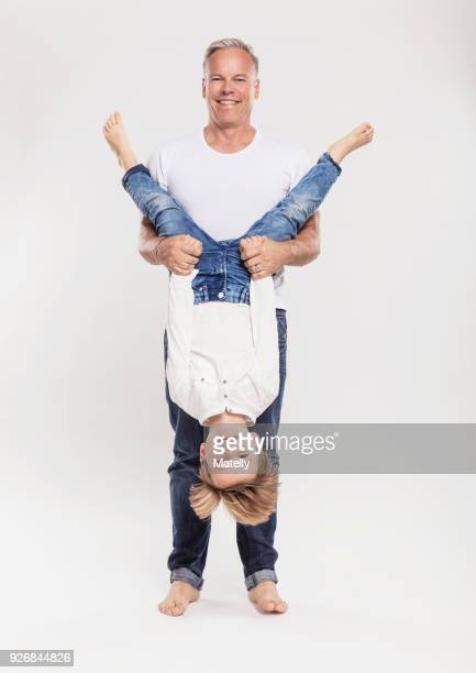 portrait of father with son held upside down - op z'n kop stockfoto's en -beelden