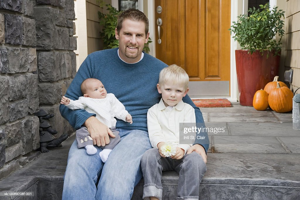 Portrait of father with young boy (4-5) and baby boy (2 months) on front steps : Stockfoto