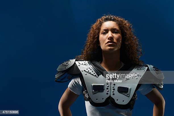 portrait of female american footballer wearing shoulder pads - padding stock photos and pictures