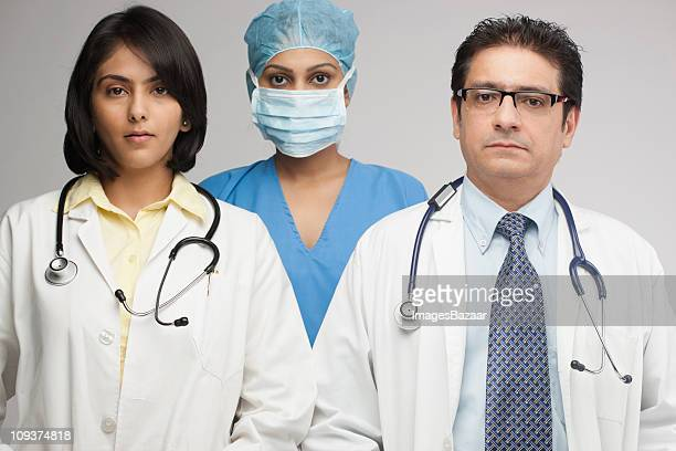 Portrait of female and male doctors with surgeon in between
