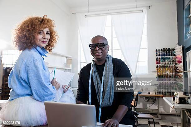 Portrait of female and male fashion design team in design studio