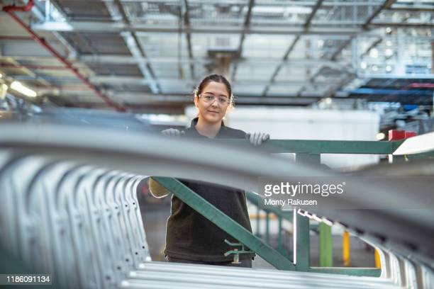 portrait of female apprentice with car parts in car factory - place of work stock pictures, royalty-free photos & images