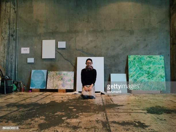 スタジオで座っている女性アーティストの肖像画