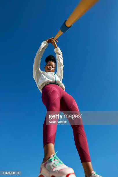 portrait of female athlete holding javelin against clear blue sky - red trousers stock pictures, royalty-free photos & images
