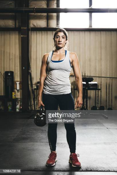 portrait of female athlete holding kettlebell in gym - female bodybuilder stock pictures, royalty-free photos & images
