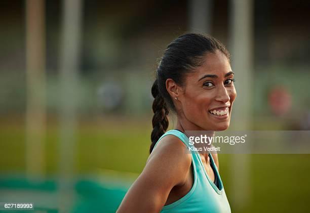 Portrait of female athlete laughing, at stadium