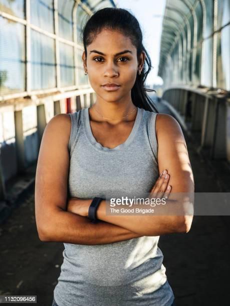 Portrait of female athlete standing on bridge